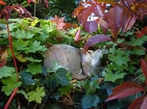 Die Keramik-Mieze von Margrit Mitterer-Meier hält ein Nickerchen auf der Gartenmauer