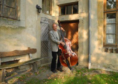 Heiner mit Bass im Obsthof vor dem Konventeingang