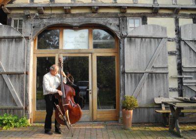 Heiner mit Bass vor der Werkstatt