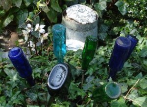 Bunte Glasflaschen ins Beet gesteckt...